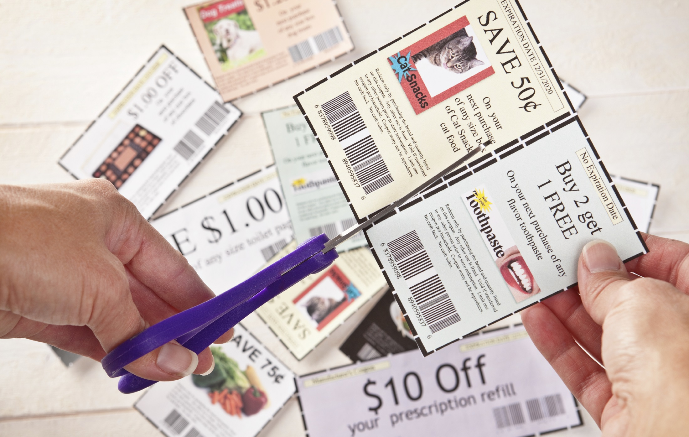 Woman's Hands Cutting Coupons