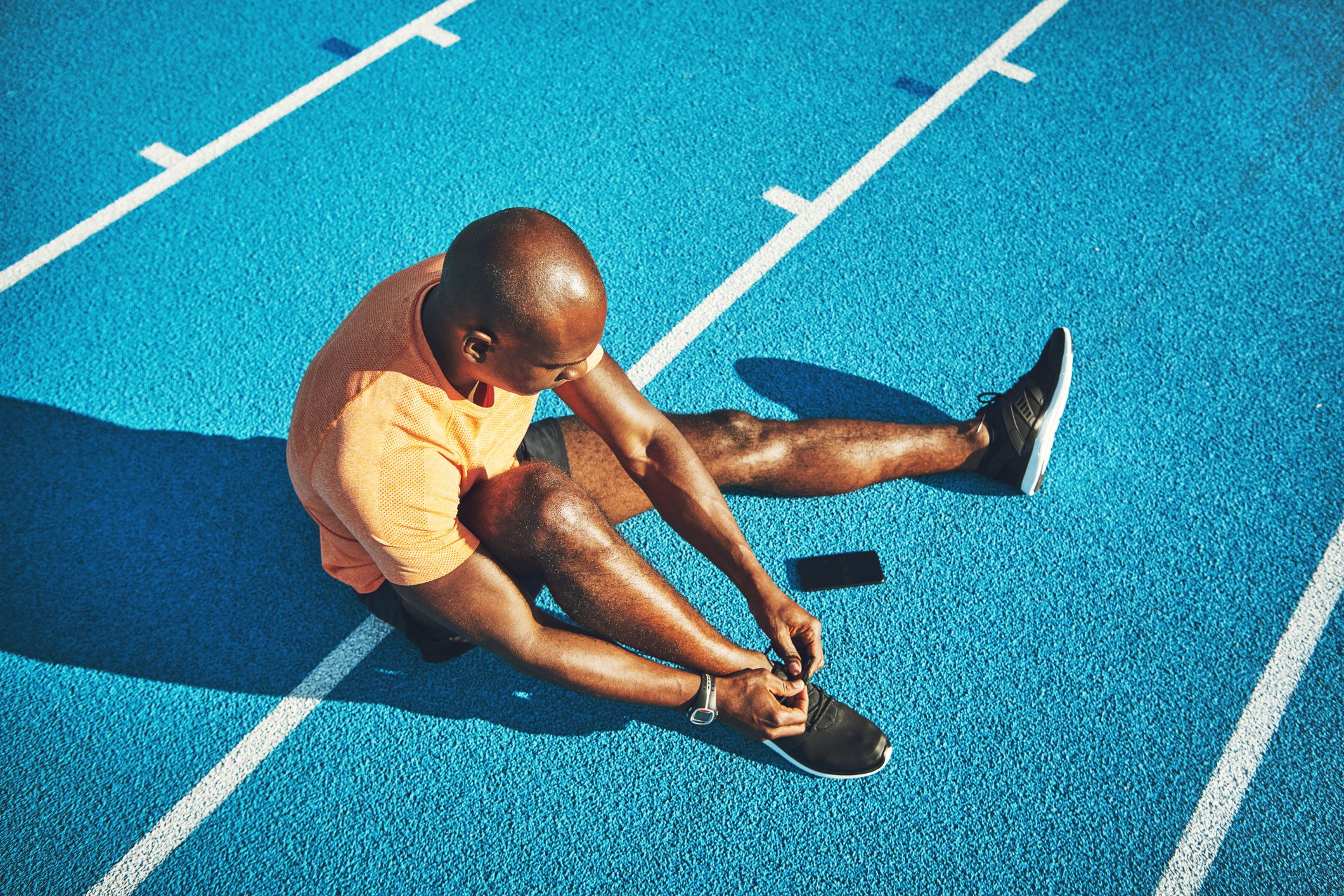 young-athlete-tying-up-his-shoes-on-a-running-track-royalty-free-image-911667868-1535048466
